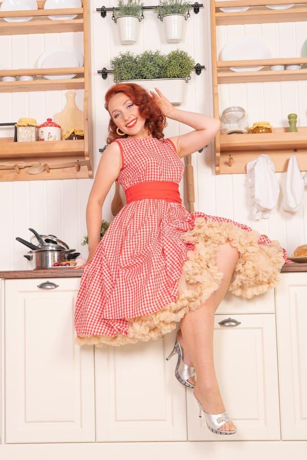 Beau pin-up roux souriant heureusement fille posant dans une rétro robe rouge dans seule la cuisine image stock