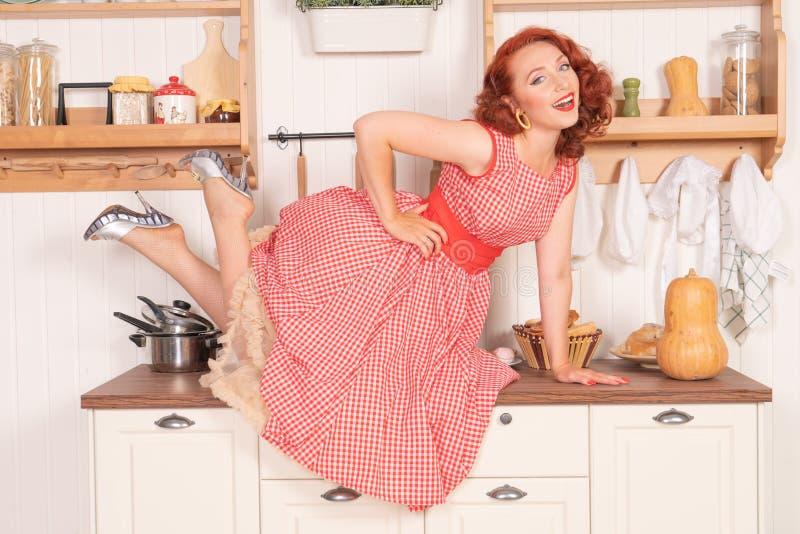 Beau pin-up roux souriant heureusement fille posant dans une rétro robe rouge dans seule la cuisine photographie stock