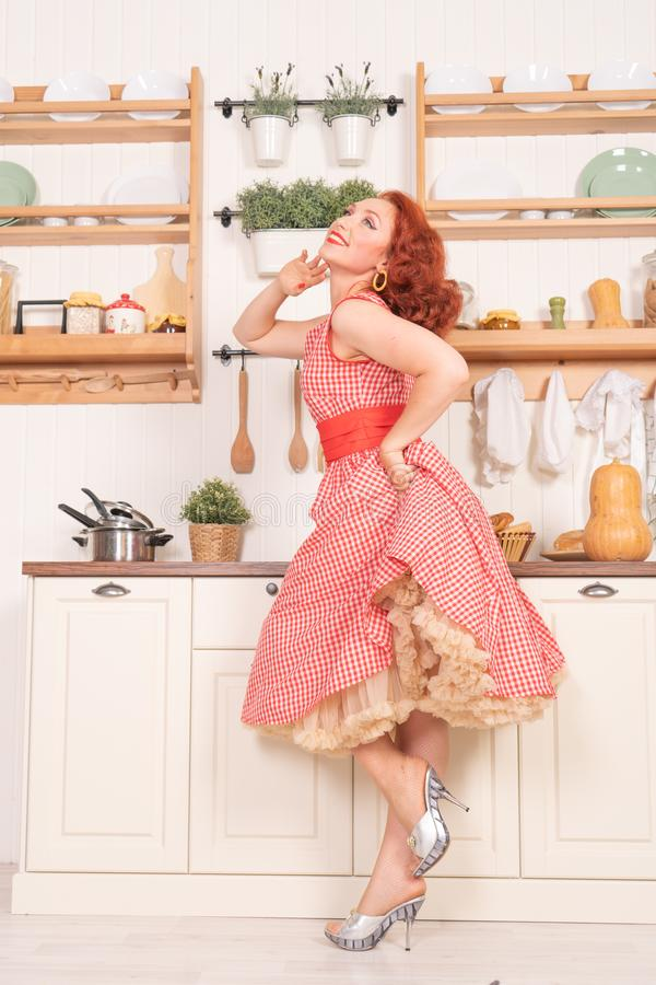 Beau pin-up roux souriant heureusement fille posant dans une rétro robe rouge dans seule la cuisine images stock
