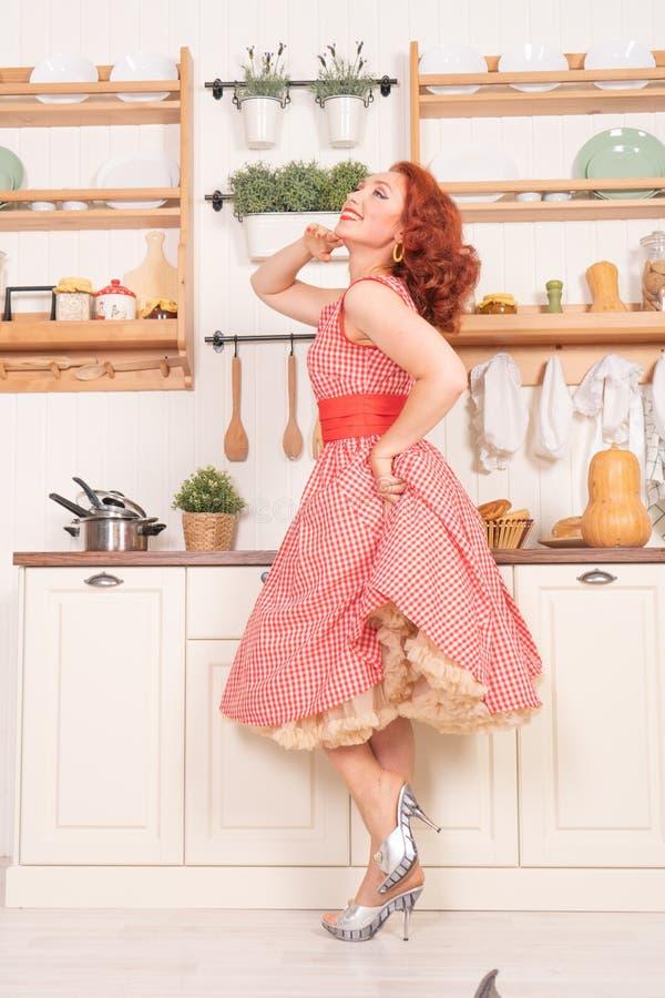 Beau pin-up roux souriant heureusement fille posant dans une rétro robe rouge dans seule la cuisine image libre de droits