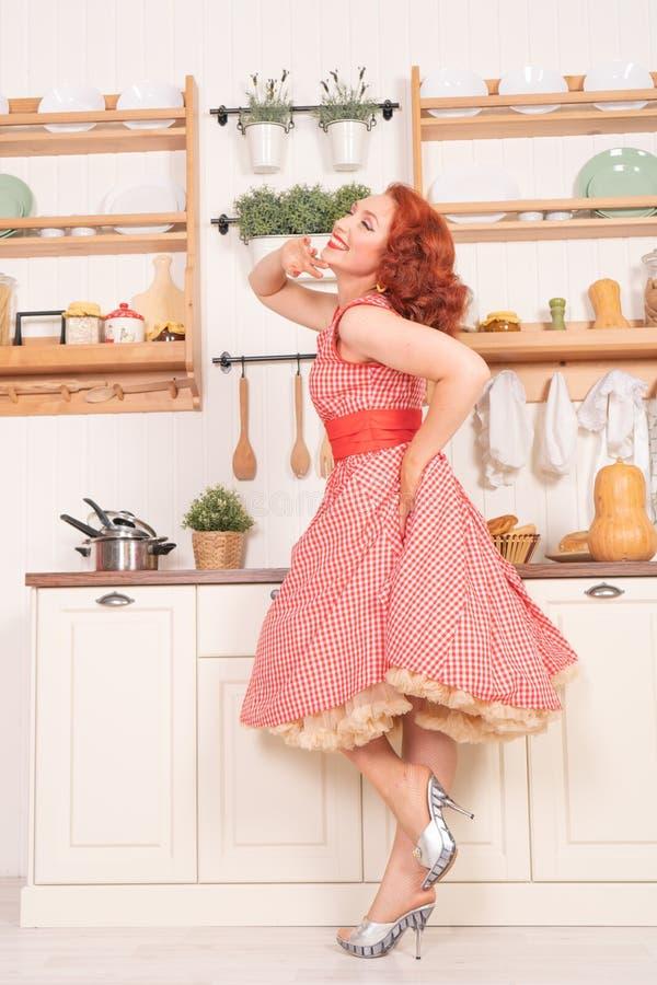 Beau pin-up roux souriant heureusement fille posant dans une rétro robe rouge dans seule la cuisine photos stock