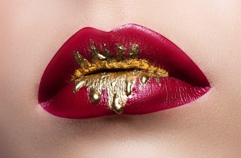 Beau plan rapproché femelle de languettes Rouge à lèvres rouge, peinture d'or circulant sur ses lèvres Photo courante photo stock