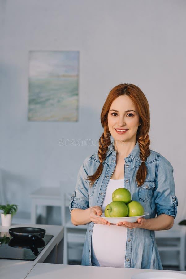 beau plat de participation de femme enceinte avec les pommes mûres photographie stock libre de droits
