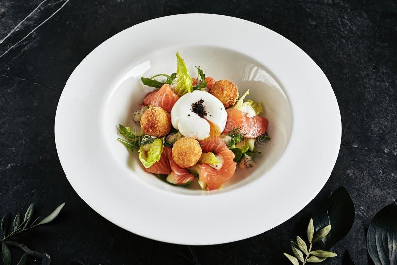 Beau plat de restaurant de filet de truite 48 degrés et oeuf pochés avec les pommes de terre chaudes photo libre de droits