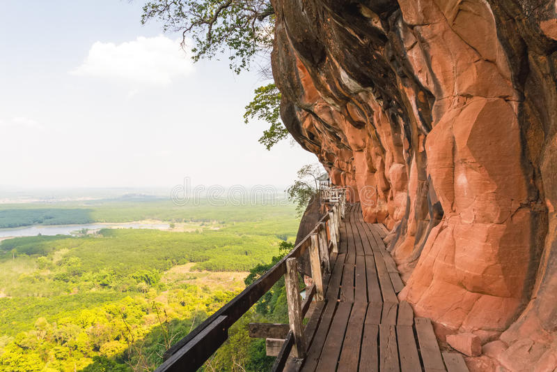 Beau pont en bois dans le cliffside rouge à la montagne de tok de Wat Phu photo libre de droits