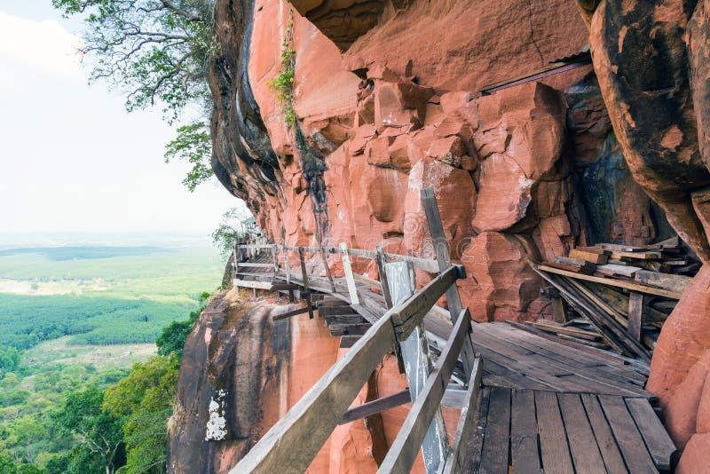 Beau pont en bois dans le cliffside rouge à la montagne de tok de Wat Phu photographie stock