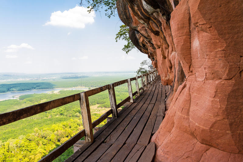 Beau pont en bois dans le cliffside rouge à la montagne de tok de Wat Phu image stock