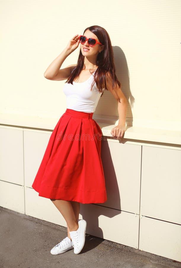 Beau port de femme de brune lunettes de soleil et jupe rouge image stock