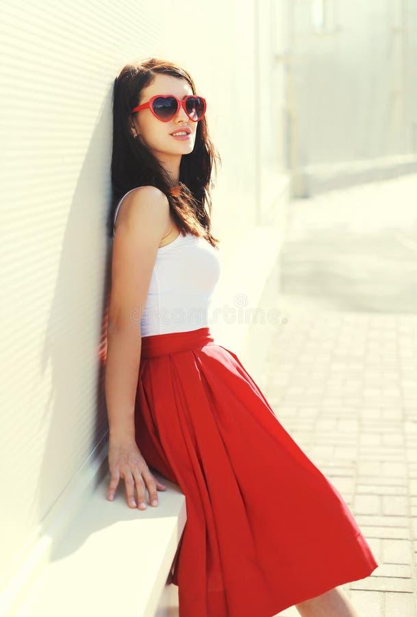 Beau port de femme de brune lunettes de soleil et jupe rouges images libres de droits