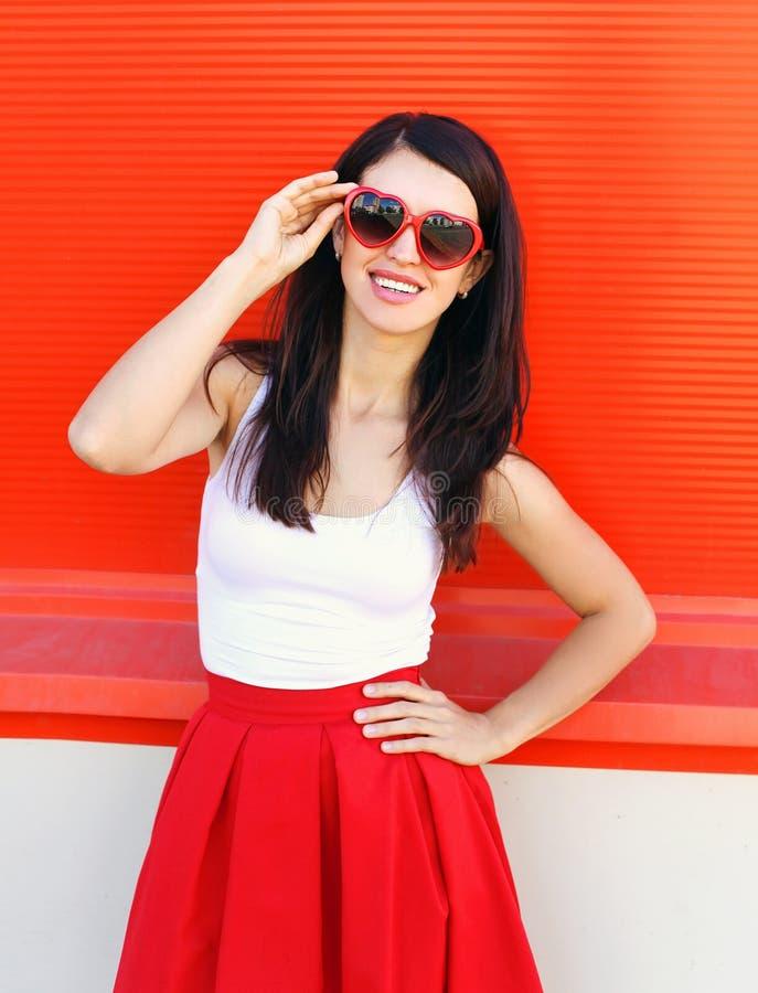Beau port de sourire de femme de brune lunettes de soleil et jupe rouges au-dessus de coloré images stock