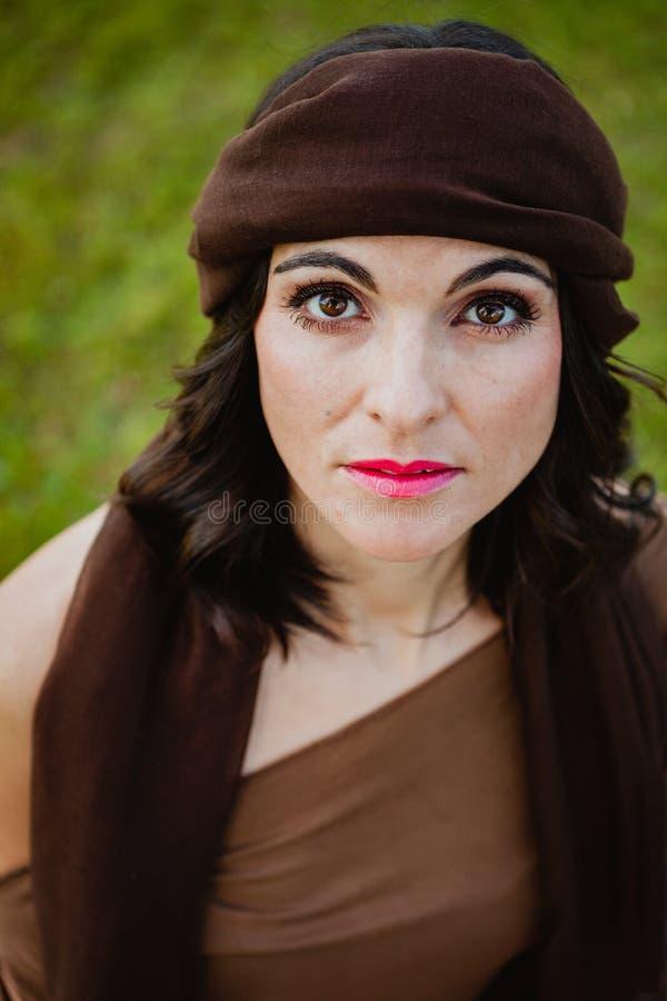 Beau portrait d'une femme de brune avec un bandana brun dans h photos libres de droits