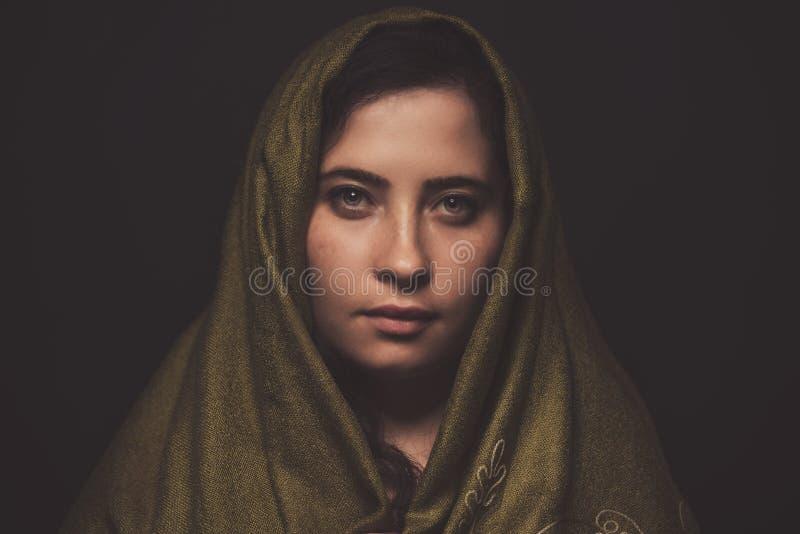 Beau portrait de femme avec l'écharpe verte au-dessus de sa tête, tir de studio photos stock