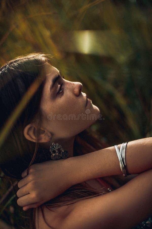 Beau portrait de jeune femme dans l'herbe au coucher du soleil photographie stock