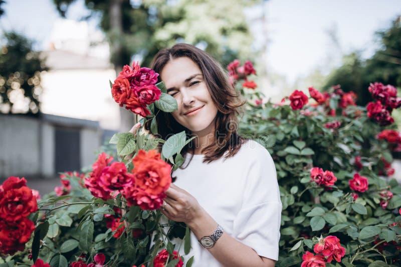 Beau portrait de jeune femme sensuelle de brune dans la robe blanche près des roses rouges Elle hidding au rosier image libre de droits