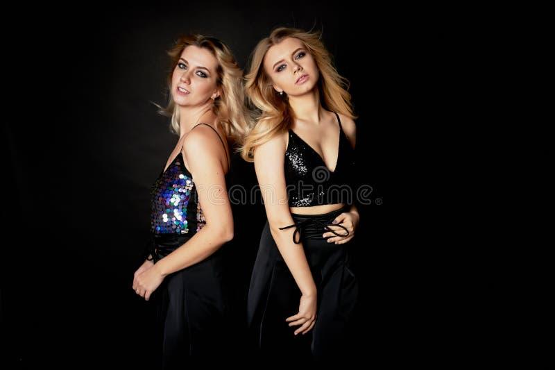 Beau portrait de mère et de fille dans le studio sur le fond noir Regardez grand Renivellement professionnel Danse et photos stock