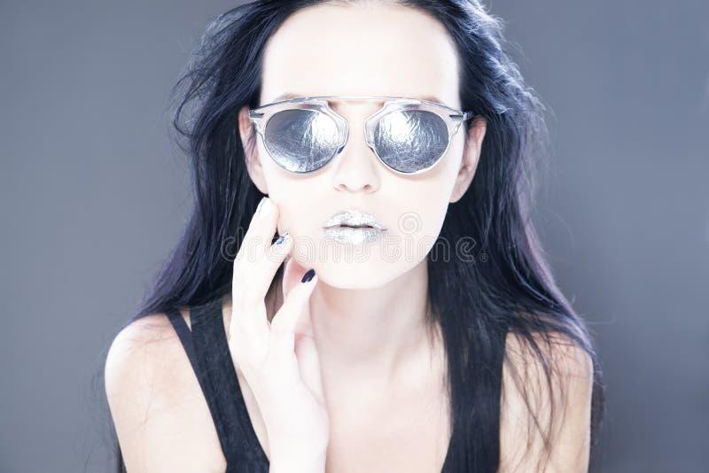 Beau portrait de mannequin de femme dans des lunettes de soleil avec les lèvres argentées métalliques La coiffure créative et com image stock