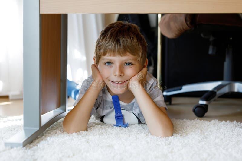 Beau portrait de sourire de Little Boy sous la table d'école Enfant heureux regardant l'appareil-photo Enfant adorable avec blond photos stock