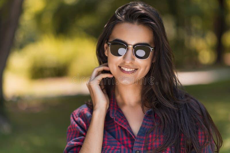 Beau portrait des lunettes de soleil de sourire de jeune brune heureuse et de port femelles caucasiennes sur le fond de nature en images stock