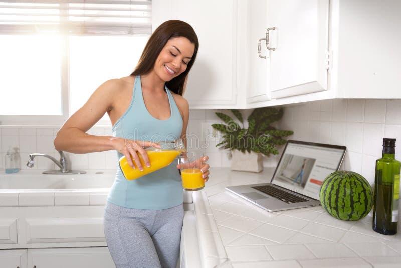 Beau portrait véritable de mode de vie d'une femelle en bonne santé et heureuse avec le verre de jus d'orange, bien-être, forme p photographie stock libre de droits
