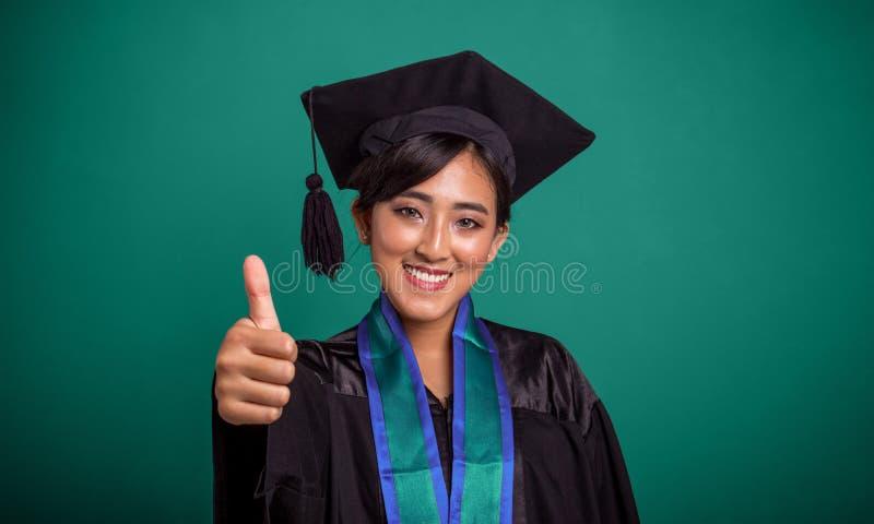Beau pouce de sourire d'étudiant de troisième cycle, au-dessus de la bannière verte photo stock