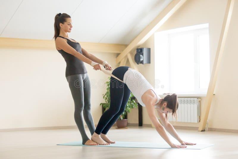 Beau professeur féminin de yogi aidant la jeune femme dans des clas de yoga photographie stock libre de droits