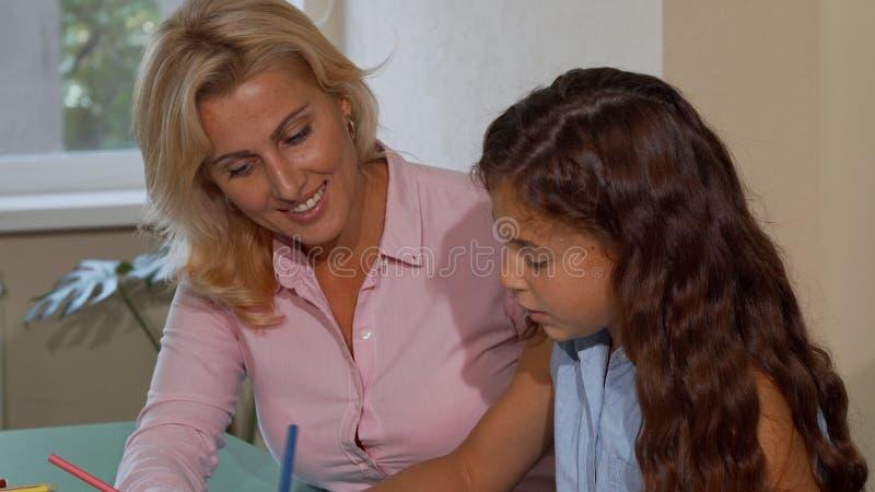 Beau professeur féminin heureux souriant tout en aidant son petit étudiant adorable photos libres de droits