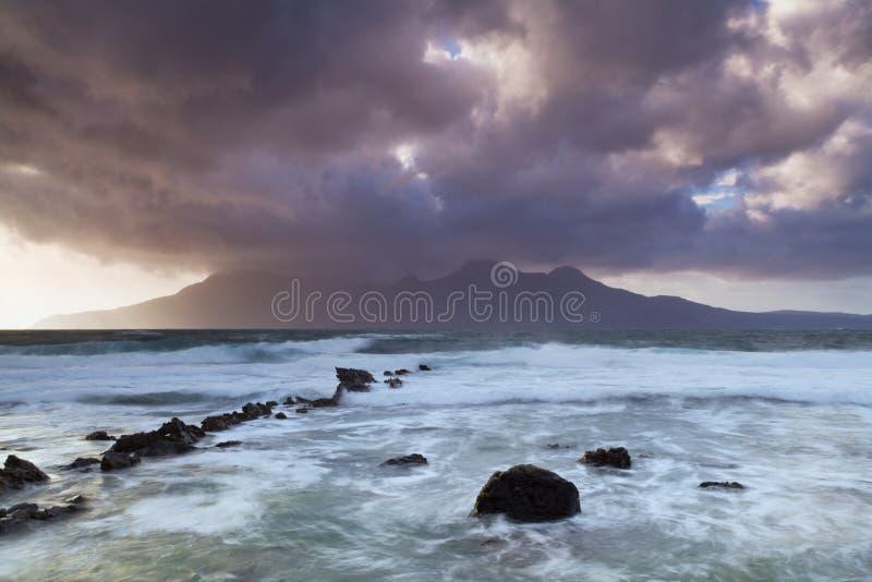 Beau, rêveur ciel et la mer dans des vagues de l'Ecosse croisant sur le rivage avec le ciel dramatique déprimé sur l'île de Skye, image stock