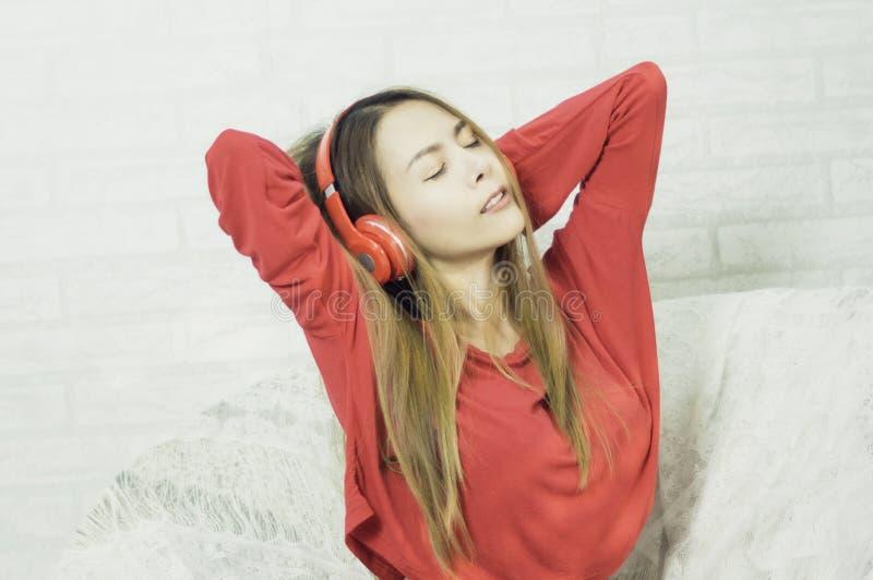 Beau repos asiatique de femme, ?coutant la musique avec les ?couteurs rouges sur le sofa et une lucette heureuse dans la maison a image libre de droits
