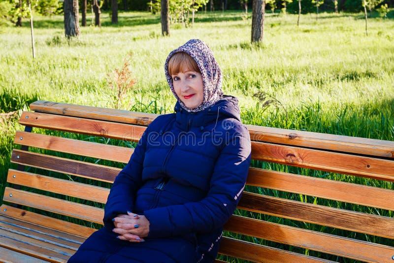 Beau retraité de femme s'asseyant sur le banc photographie stock libre de droits