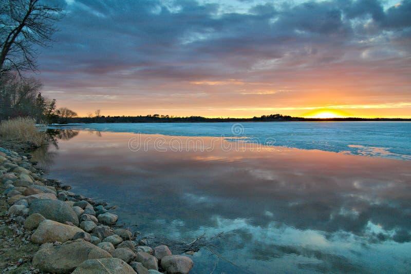 Beau rivage de lac au Minnesota au coucher du soleil avec l'eau libre et la glace image stock