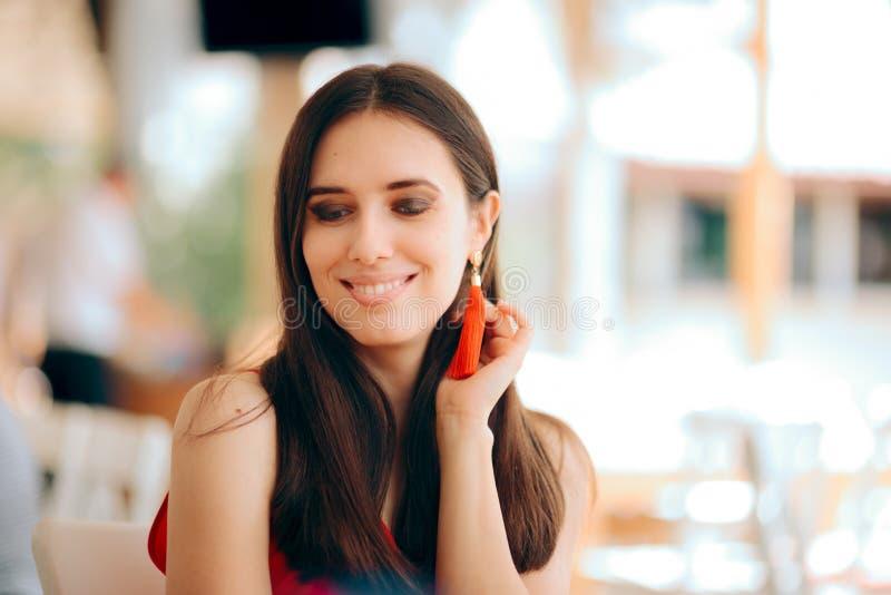 Beau rouge de port de sourire de femme et boucles d'oreille de gland photo libre de droits