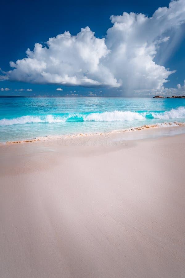 Beau roulement blanc de ressac vers la plage sablonneuse tropicale Nuages pelucheux au-dessus de mer bleue Anse grand, Seychelles photos stock