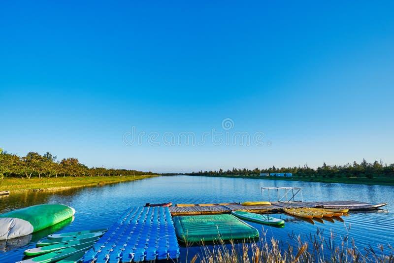 Beau scenics de lac débordant, du grand lac synthétique de parc public populaire pour nager, avec les traînées adjacentes de vélo photographie stock libre de droits