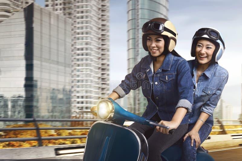 Beau scooter d'équitation de femme de deux Asiatiques ensemble image libre de droits