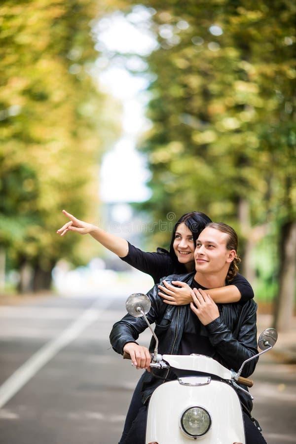 Beau scooter heureux d'équitation de couples et sourire amusement de avoir, femme dirigée avec des mains et photos libres de droits