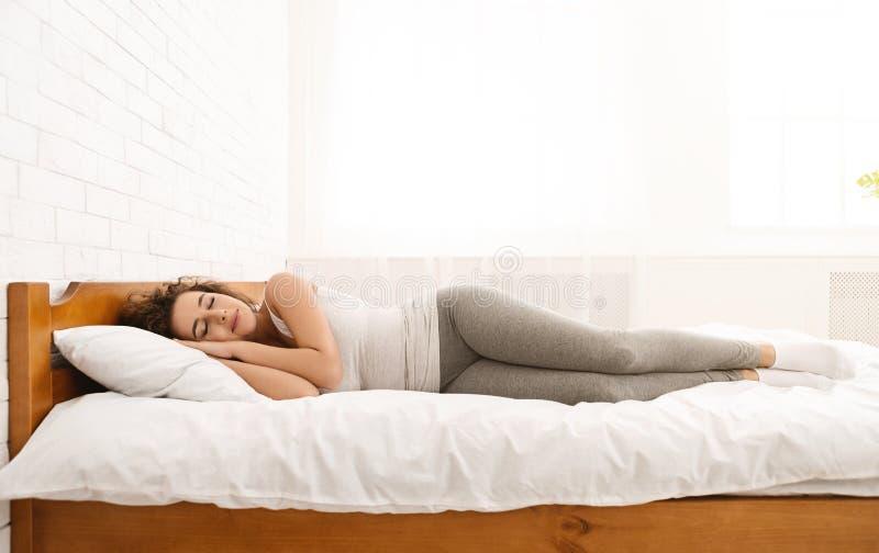 Beau se situer de sommeil de jeune femme dans son lit photographie stock libre de droits