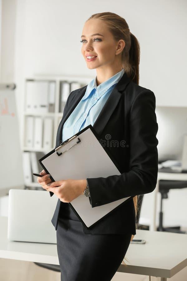 Beau secrétaire féminin avec le presse-papiers dans le bureau photo libre de droits