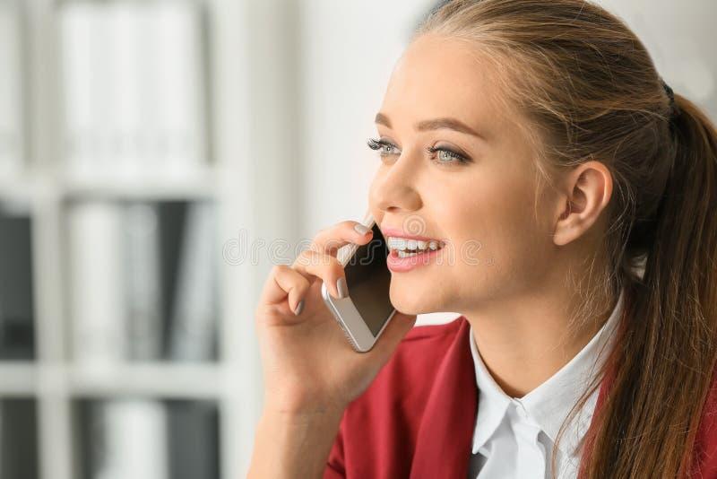 Beau secrétaire féminin parlant au téléphone portable dans le bureau photos libres de droits