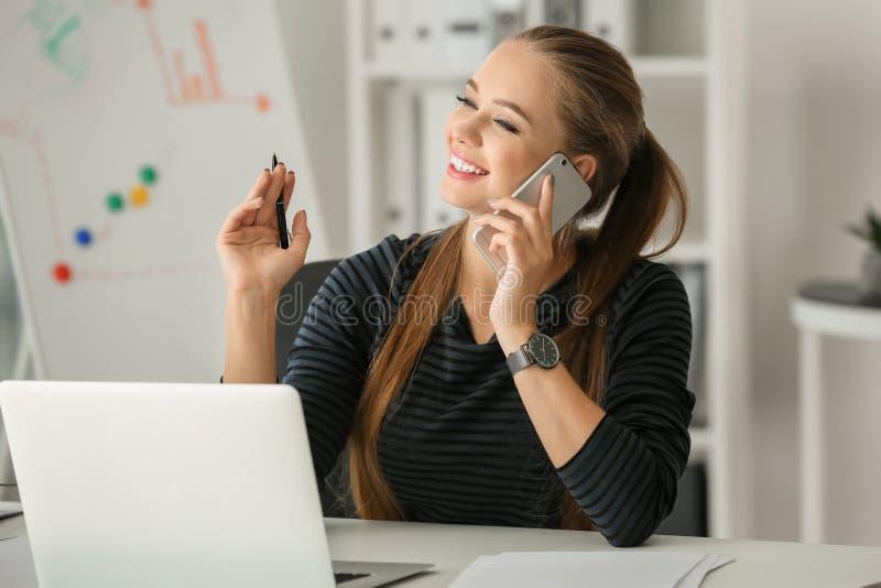 Beau secrétaire féminin parlant au téléphone portable dans le bureau photo libre de droits