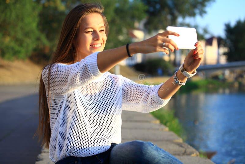 Beau selfie de jeune femme en parc avec un smartphone photographie stock