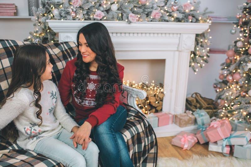 Beau SIS de jeune femme et de fille sur le sofa et regarder l'un l'autre Ils sourient Les gens sont dans la chambre décorée mère photographie stock