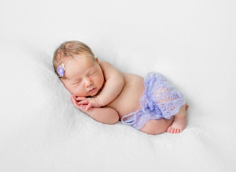 Beau sommeil nouveau-né avec des mains sous la tête dans des culottes violettes images stock