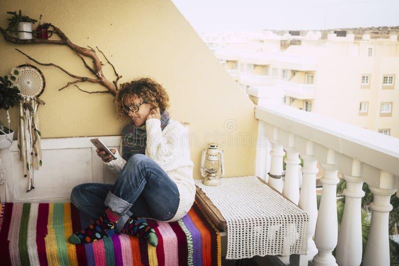 Beau sourire caucasien de femme tandis que travail à la maison extérieur sur la terrasse avec un ordinateur portable et un téléph photos stock