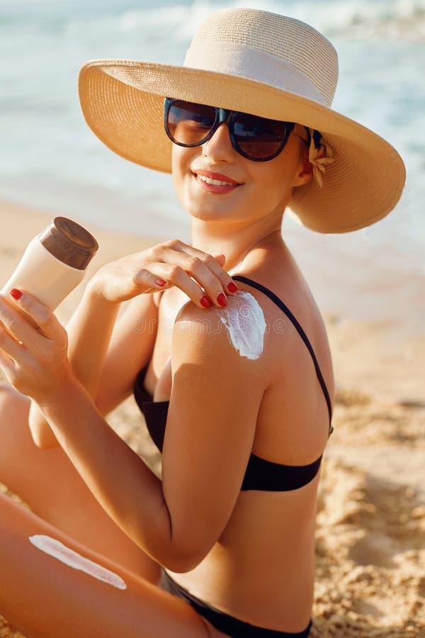 Beau sourire de femme appliquant la crème du soleil sur l'épaule Soins de la peau Protection de Sun de corps sunscreen Femelle ut photo stock