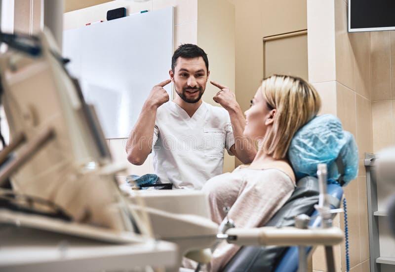 Beau sourire sain pendant la vie Le dentiste explique en d?tail le progr?s du traitement dentaire patient dans moderne image stock