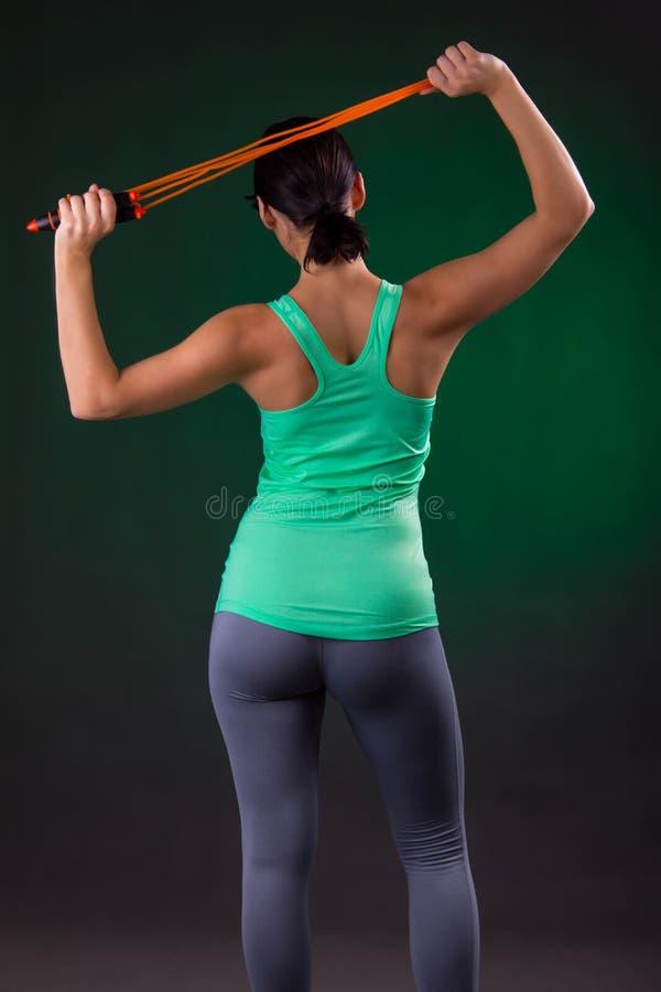Beau sportif, position de femme de forme physique, posant avec une corde de saut sur un fond gris avec un contre-jour vert images stock