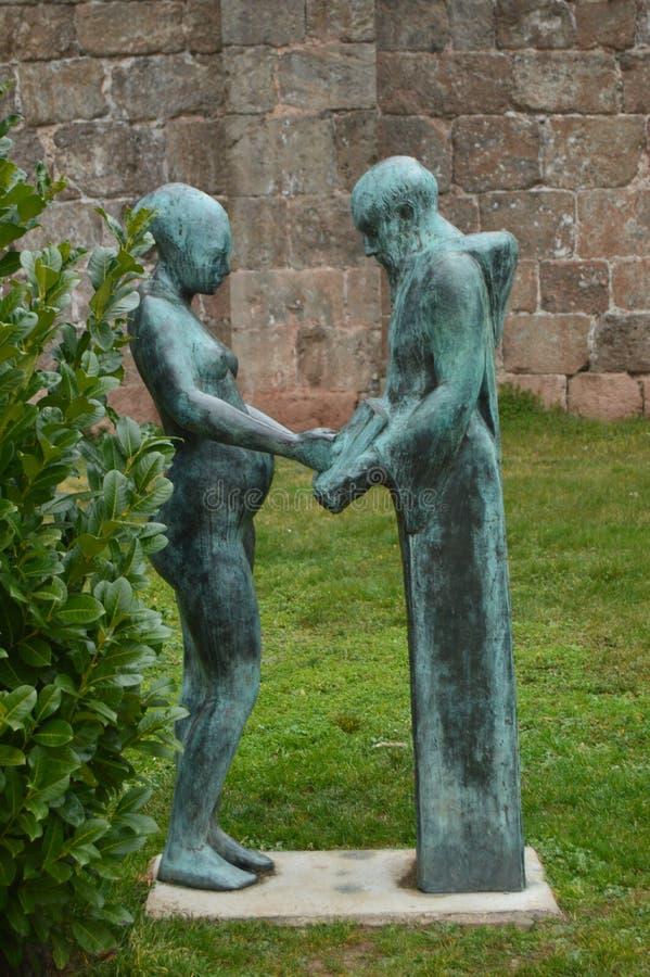Beau statut d'un moine et d'une femme dans les jardins du monastère de San Millan de La Cogolla un jour très nuageux Architec image stock