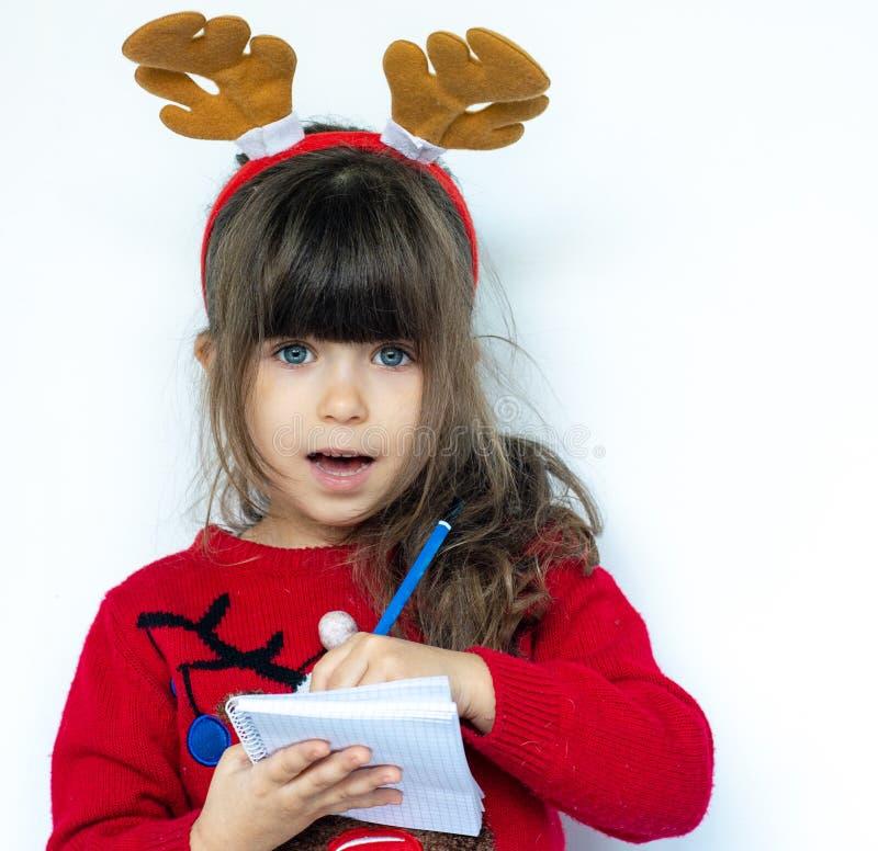 Beau stylo de participation choqué d'enfant et inscription une liste d'achat du portrait riant drôle d'enfant Nouvelle année s photographie stock