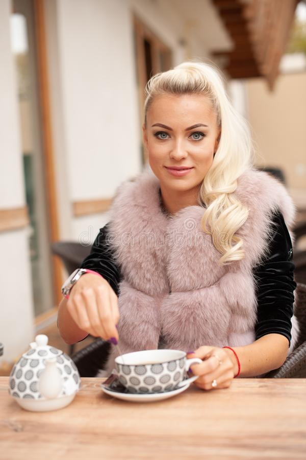 Beau thé de boissons de jeune femme sur le terace de barre en automne tôt photos stock