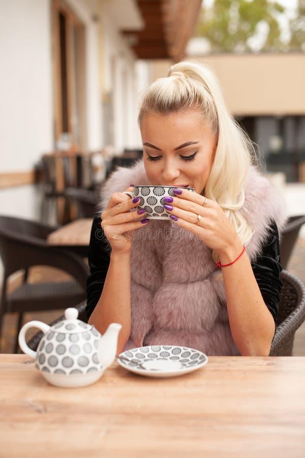 Beau thé de boissons de jeune femme sur le terace de barre en automne tôt photographie stock